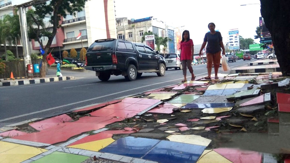Pejalan kaki melewati trotoar rusak