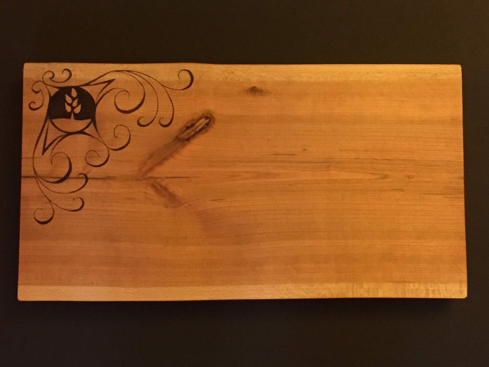 Live-edge  Cherrywood Cuttingboard with synagogue logo and decorative accents wood burnt by hand.