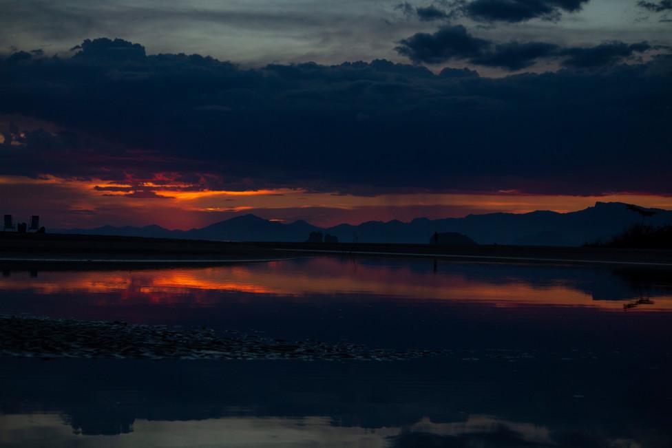 Sunset at Fazenda Beach with summer rain showers and views of Serra do Mar mountains