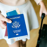 Closeup of girl holding passports and bo
