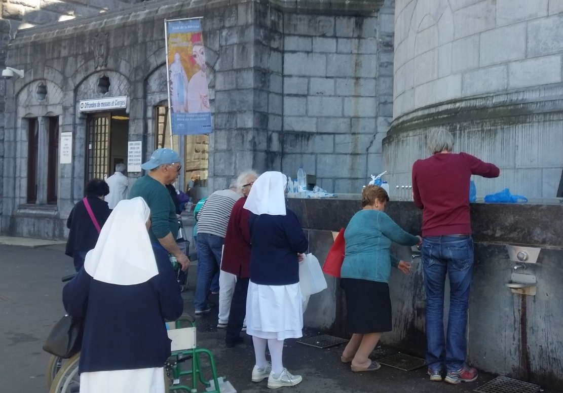 Fetching holy water in Lourdes