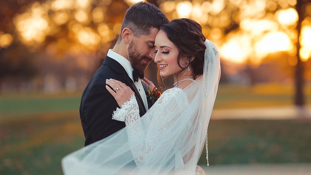 Groom in black tux with bride in white dress on golf course at sunset