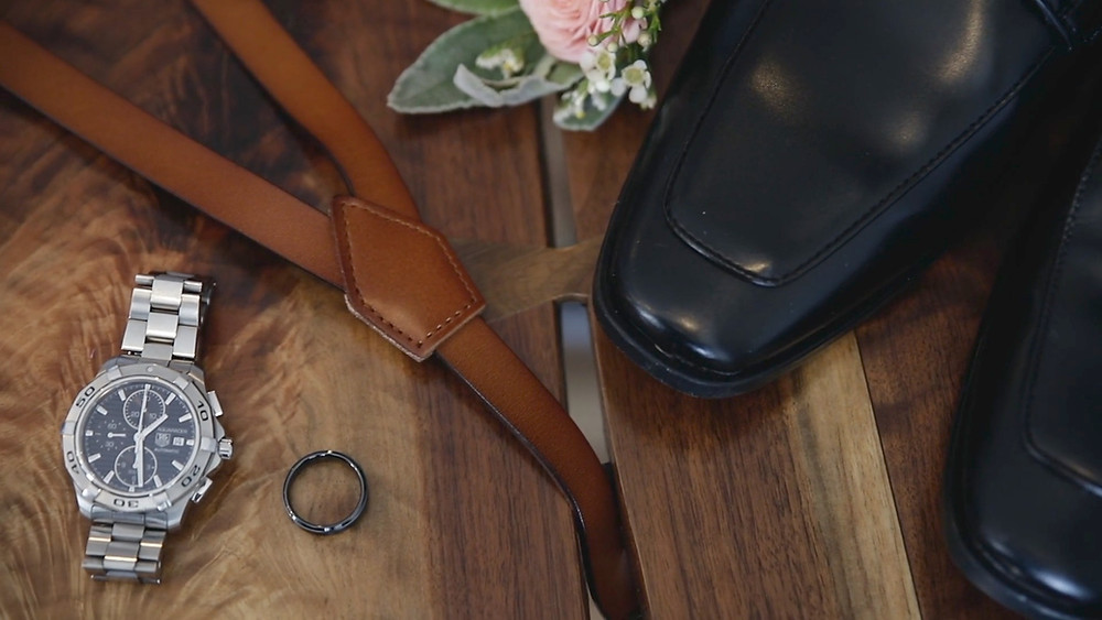 Groom items on table with watch
