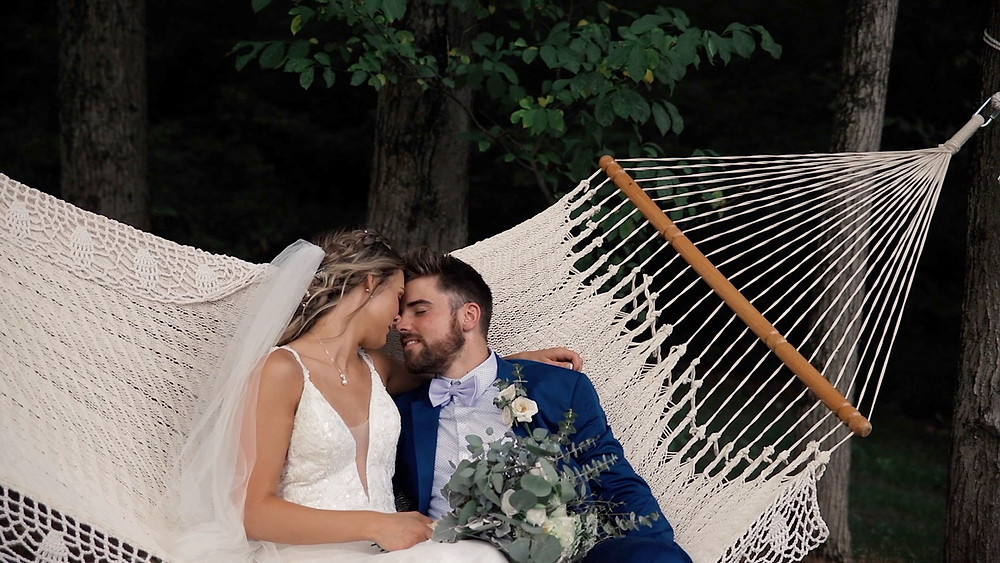Bride in white dress and veil with groom in blue tux sitting in a white boho hammock