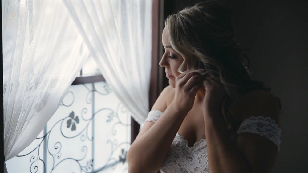 Bride in white dress putting earring in infront of window strata wedding films
