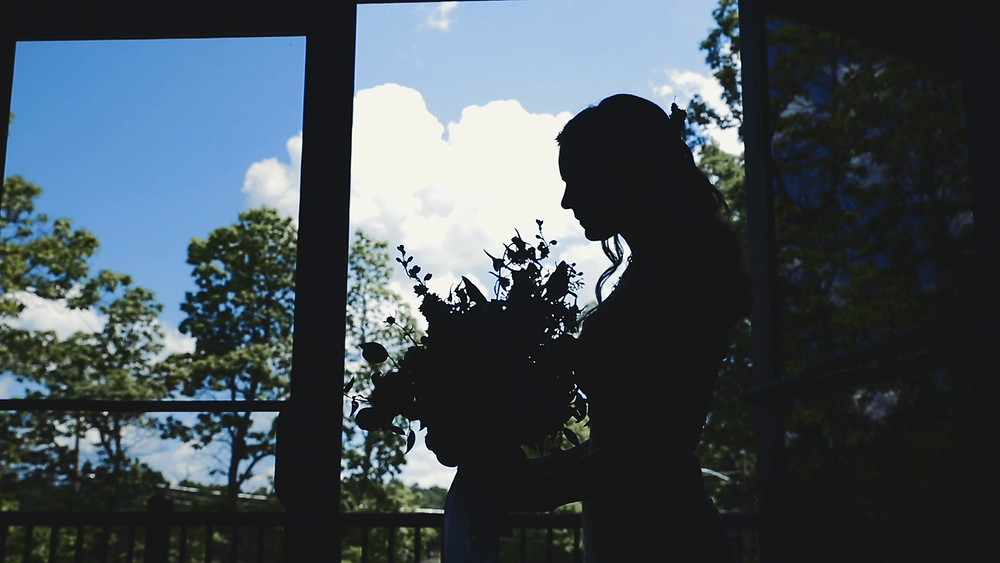 Bride holding boquet silhouette in front of window