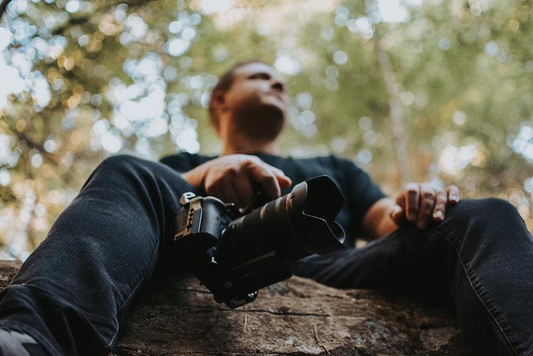 sitting on rock holding camera canon r6 strata wedding films