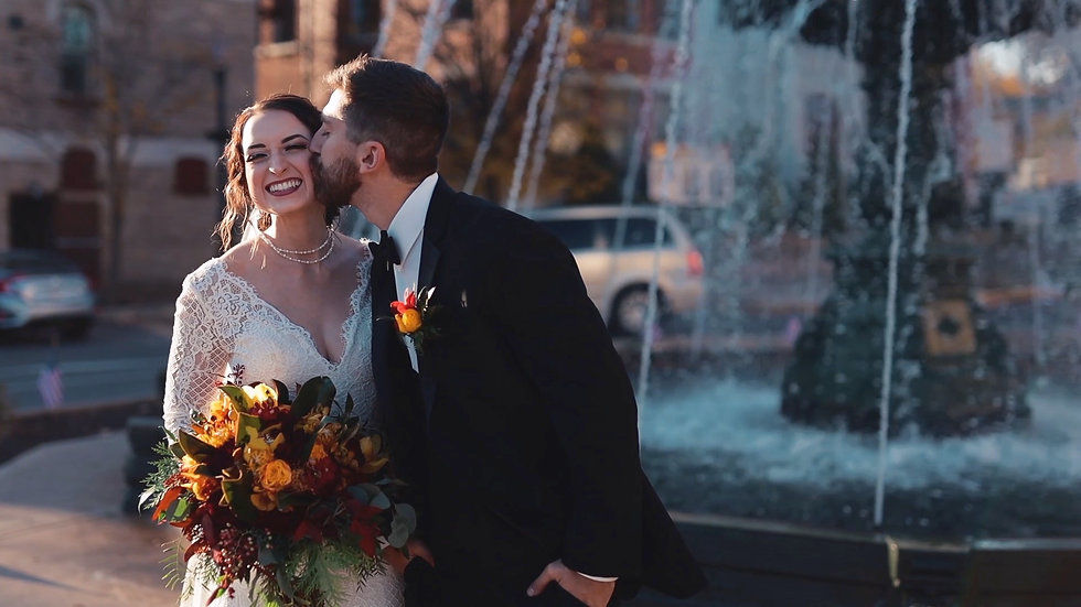 Groom in black tuxedo kissing smiling bride in white dress infront of a fountain bloomsburg pa