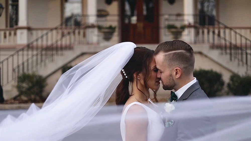 bride in white dress with long veil kissing groom in gray tux infront of a mansion strata wedding films