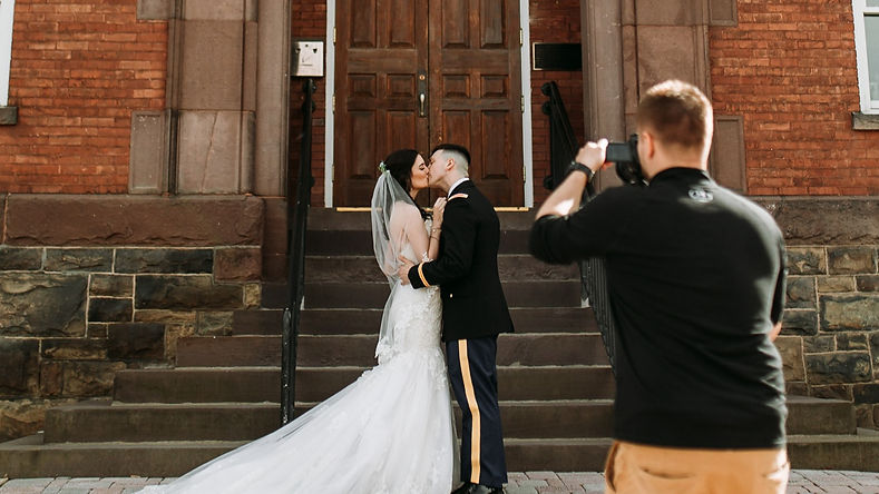 strata wedding films filming bride and groom kissing infront of building groom in uniform
