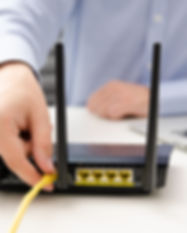 Man plugs Ethernet cable into router. ro