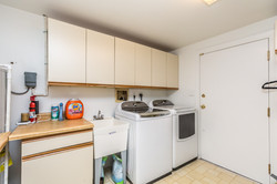 Laundry room with door to trash room and storage