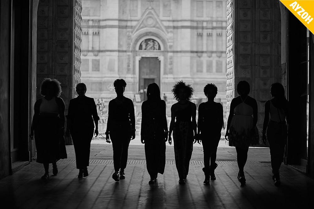 un gruppo di ragazze in penombra che cammina.
