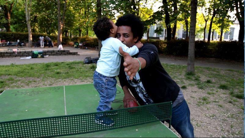 Un bambino sopra ad un tavolo da ping pong abbraccia un uomo.