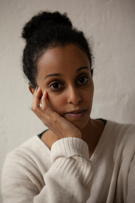 Una ragazza con i capelli raccolti che guarda la camera con una mano appoggiata sotto la guancia mento. Ha un espressione seria