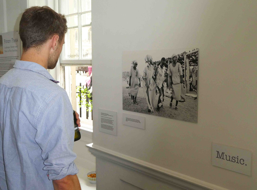 Milo Newman, who assisted with hanging the exhibition, looks at image by photographer Sylvia Diez