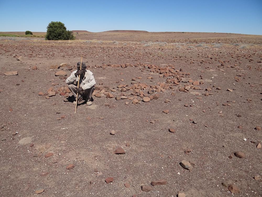 Ruben Sanib at circle of stones marking the dwelling of a family he remembers living at Kai-as (photo: Sian Sullivan, 231114).