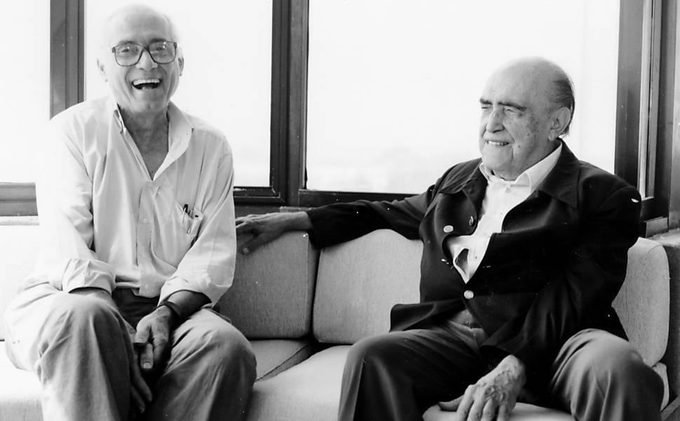 Lelé e Oscar Niemeyer seduti su un divano insieme. Entrambi sorridono.