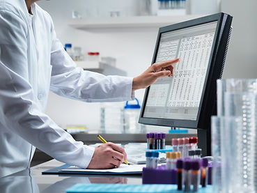 Someone in a white labcoat is standing in front of a computer screen and counter. Their left hand is pointing to an item on the screen filled with text, their right hand is resting on the counter, with a pencil in hand. Vials of substances are standing in holders on the counter.