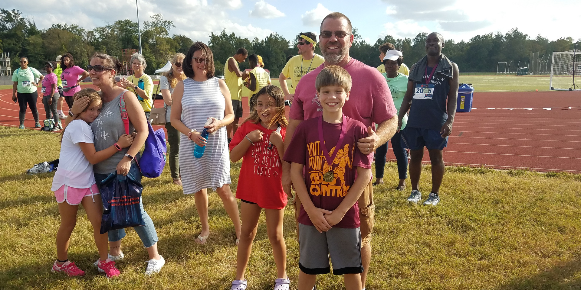 Middle School Boys' Mile 1st-place medalist and family are all smiles