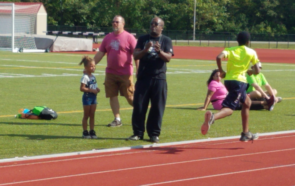 Middle School Boys' Mile runner sprints for the finish line