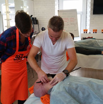 Demonstrating a wet shave facial for beauty treatment.