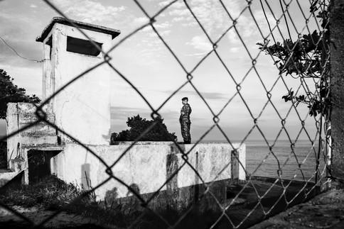 Military man through the fence, Rio de Janeiro, Brazil, 2014