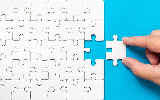 hand-putting-piece-white-jigsaw-puzzle-b