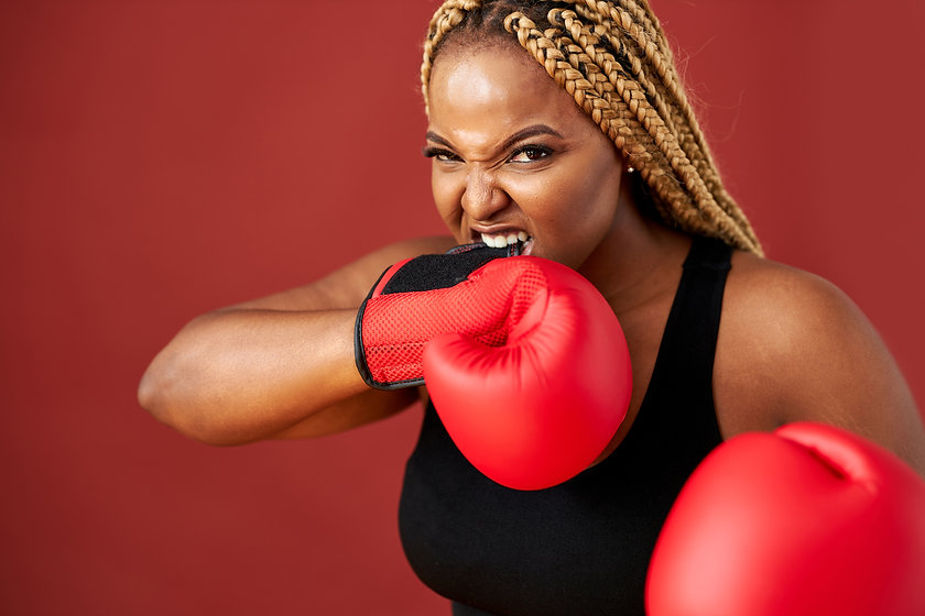 african oversize woman with red boxing mitts isolated on red background, beautiful dark-sk