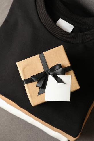 ढेर-स्टाइलिश-स्वेटशर्ट-साथ-उपहार-बॉक्स-ऑन-कुर्सी-2021-04-06-19-05-40-utc.jpg