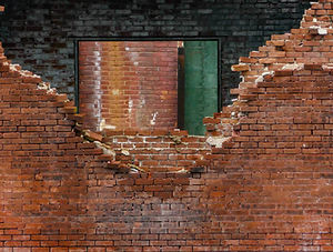 A crumbling red brick wall needing repair