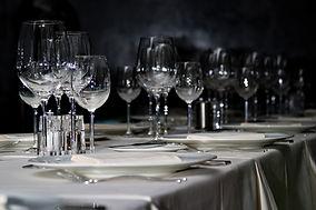 Gedeckter Tisch mit Weingläser, Besteck und Teller. Bild mit dunkelm Hintergrund