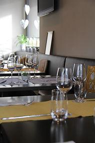Innenansicht Toblers Wirtshaus Wichlern: gedeckte Tische mit gelber Tischläufer und Gläsern