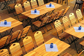 Holztische mit Stühlen, kleines blau-kariertes Tischtuch und blaue Kerzengläser