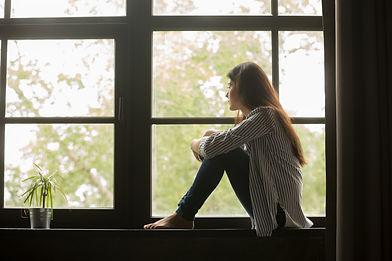 Thoughtful girl sitting on sill embracin