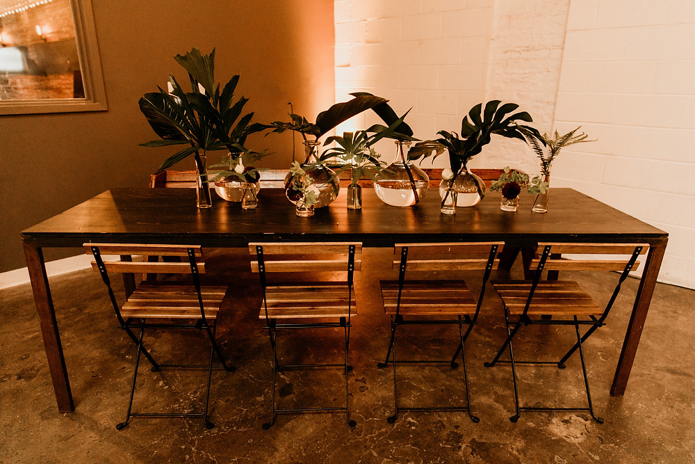 Modern, industrial wedding design in San Francisco gallery including foliage, bud vases, and candles.