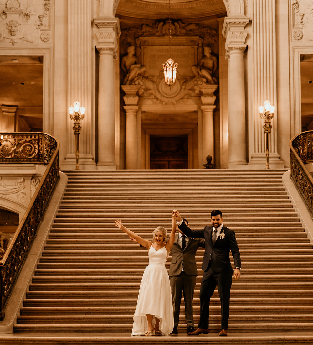 San Francisco City Hall wedding ceremony in a modern wedding dress and tailored groom's suit.