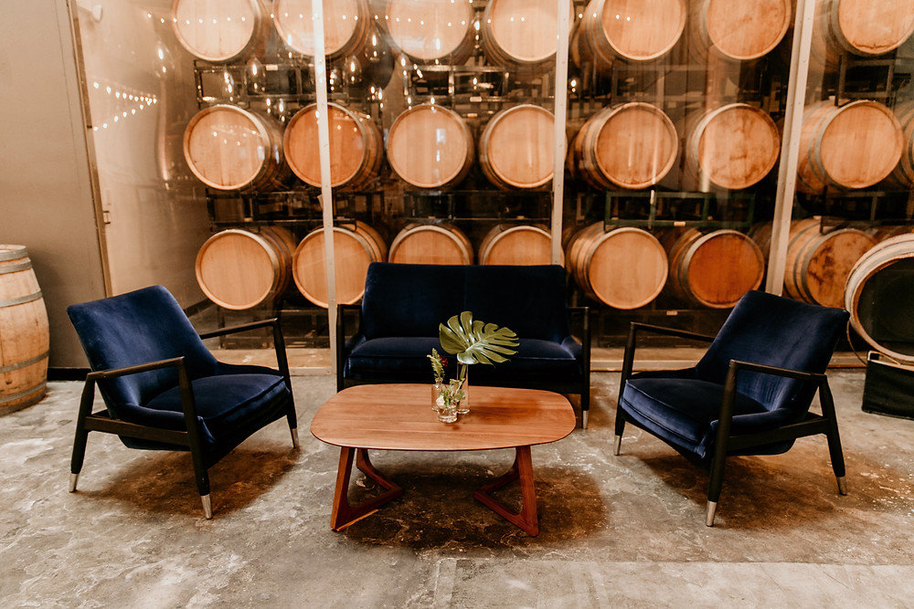 San Francisco industrial wedding meets modern design elements through rented lounge furniture, foliage, and wine barrels.