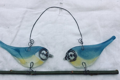 A pair of fused glass blue tits on a twig