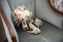 Brides wedding shoes with a bouquet with