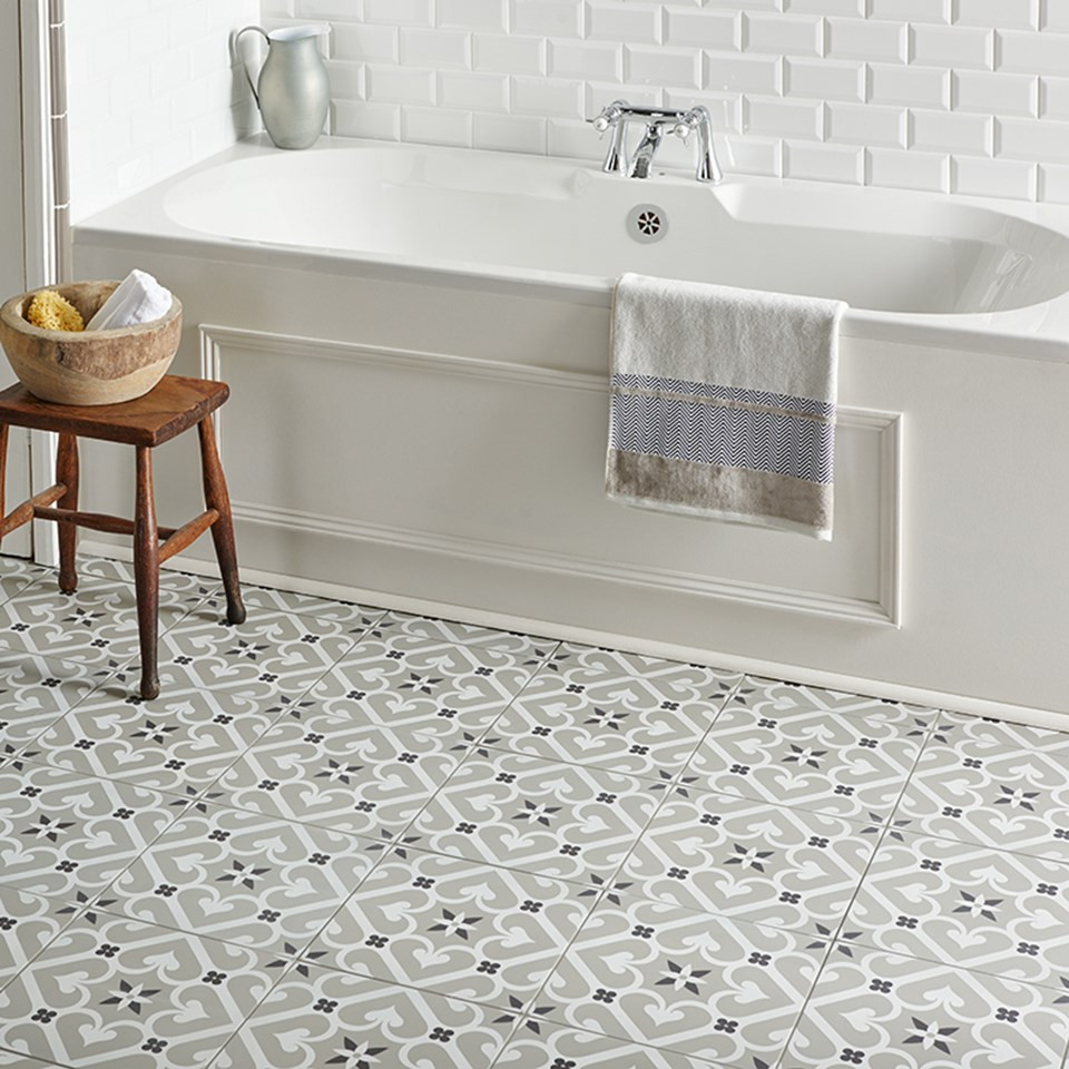 Bathroom with victorian Tiles in light grey, white and black geometric pattern and a white built in bathtub