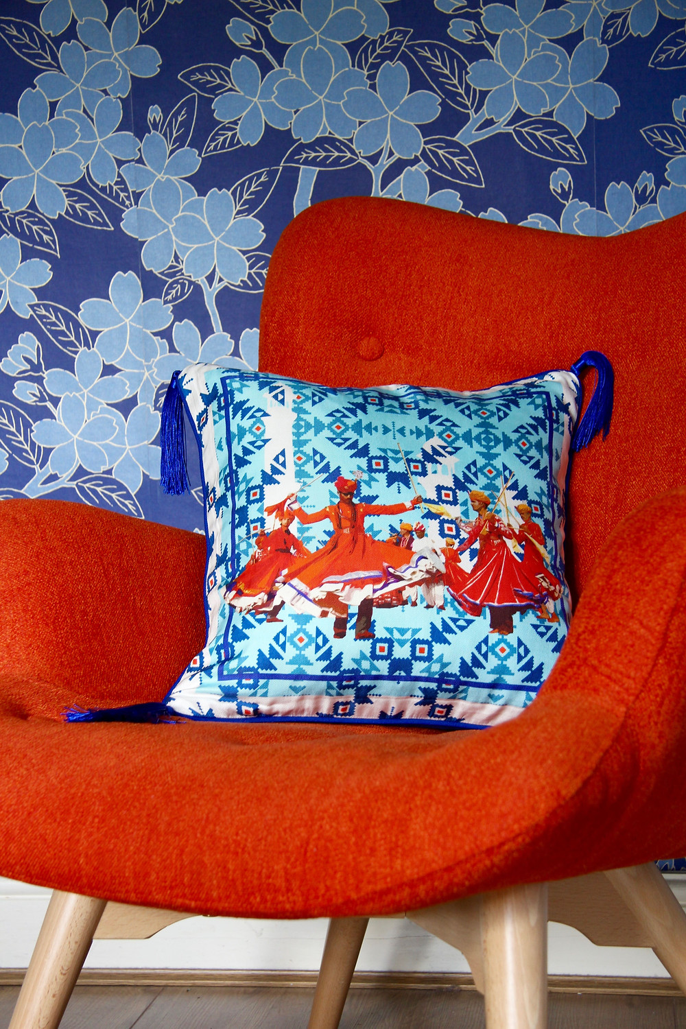 Blue cushion by BIVAIN in silk twill in a blue background and on a Sloane and Sons tub chair in orange colour