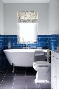 Gemini tiles Vivid tiles as a border in the bathroom, freestanding silver claw roll top bathtub and blue metro tiles