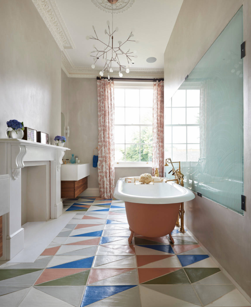 Victorian townhouse Bathroom with a Drummonds roll top cast iron bath in pink with brass taps and colourful floor tiles