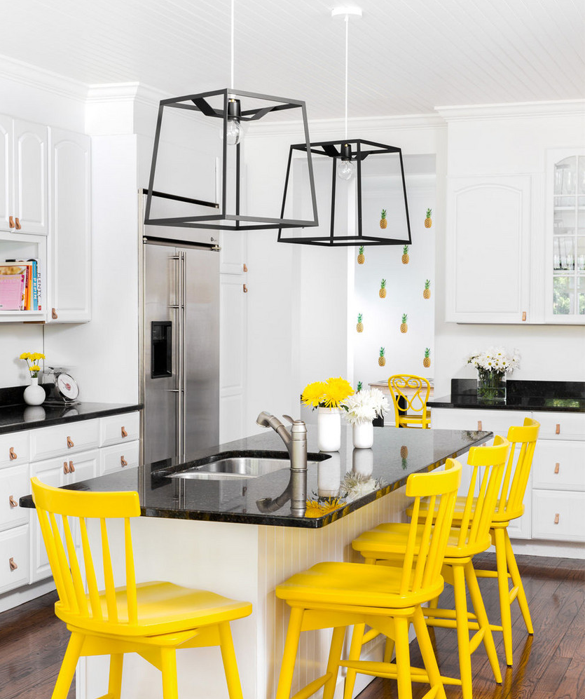 Contemporary kitchen with yellow painted chairs.