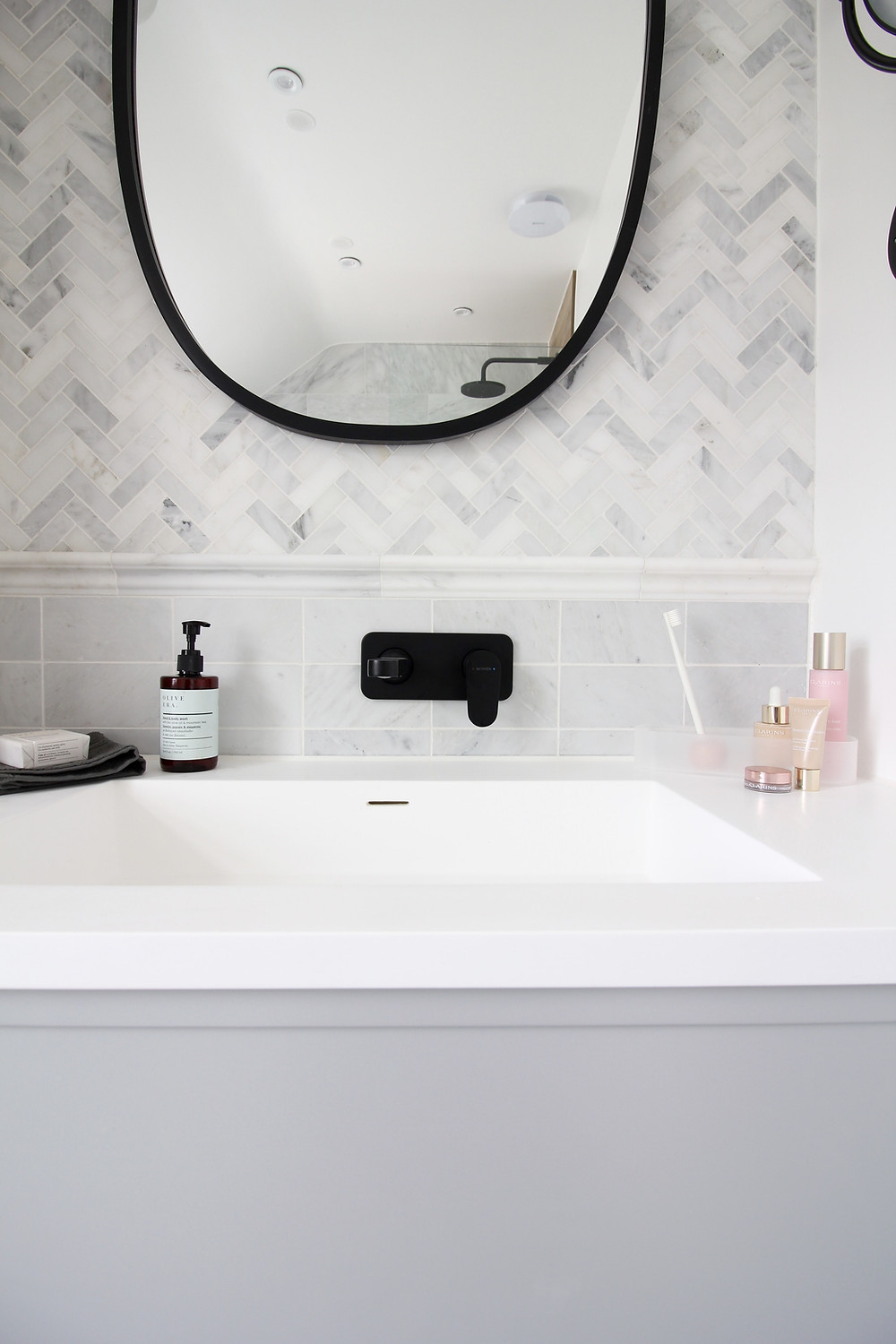 Methven Breeze wall mounted black basin mixer, marble herringbone mosaic and marble metro tiles Mandarin Stone, and the Lusso PIANA 1000 vanity with resin Stone sink, UMBRA HUB Oval mirror