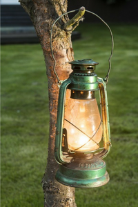 retro handcrafted lantern in green on a branch