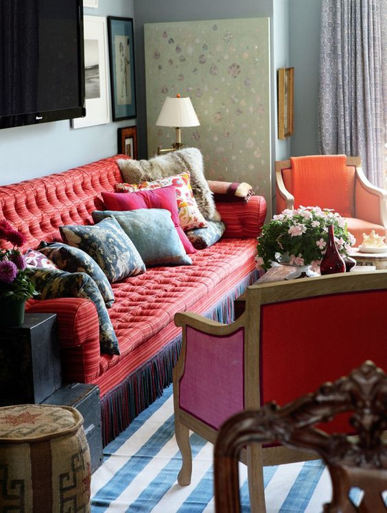 Jeffrey Bilhuber interior design with red sofa with bullion fringe