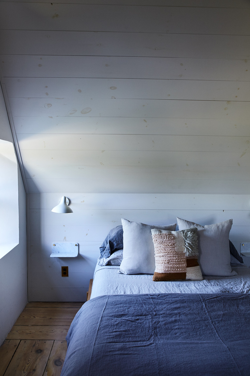 farmhouse designer bedroom decor with white wall lamp next to the bed