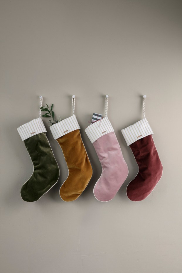 Velvet stockings hanging with presents in mustard pink and green colours from Ferm Living